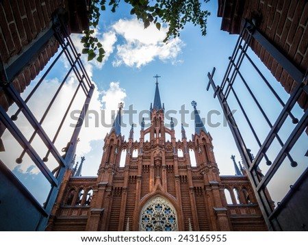 Open metallic gate towards an old Christian church with impressive architecture, under a cloudy blue sky, concept of salvation, heaven and spiritual comfort, from low-angle. - stock photo