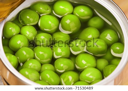 Open metallic tin can with green peas