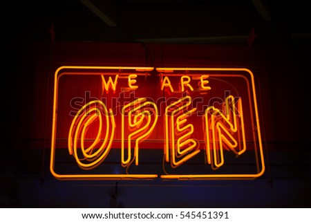 Open neon sign against dark background showing open for business