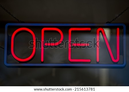 open neon sign on grey and black background