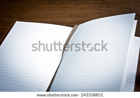 Open note book diary with empty pages on wooden table - stock photo