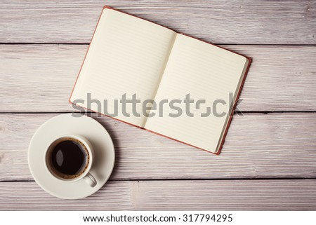 Open notebook and a cup of coffee over old wooden desk