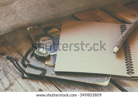 open notebook and antique photos on wooden table. retro filtered image  - stock photo