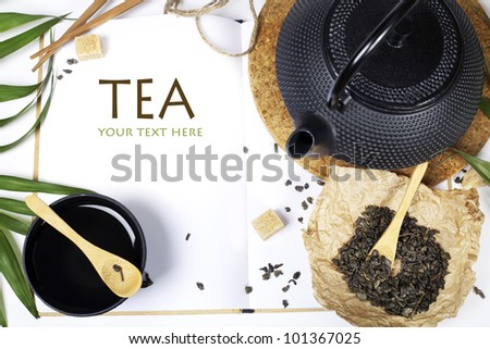 Open notebook and Asian tea set on  white background (with easy removable sample text) - stock photo