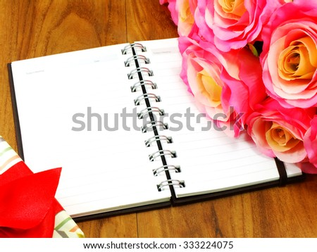 open notebook and beautiful flowers bouquet on grunge wooden background