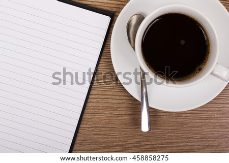 Open notebook and coffee cup on a wooden surface