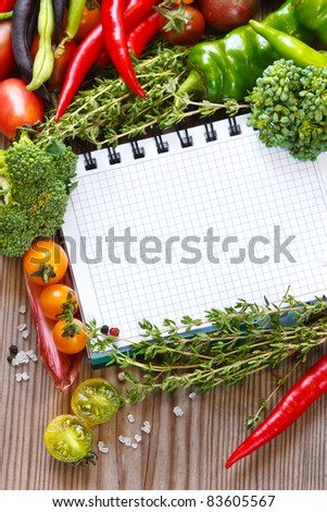 Open notebook and fresh vegetables on an old wooden board. - stock photo