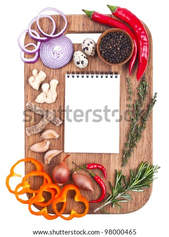 Open notebook and fresh vegetables on an old wooden cutting board. Isolated on white - stock photo