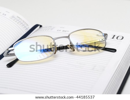 open notebook and glasses, isolated on white background