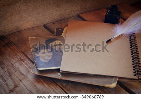 open notebook and old photos on wooden table. retro filtered   - stock photo