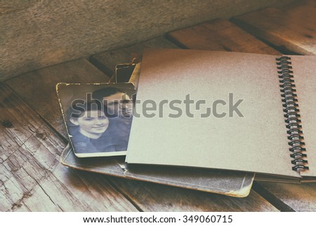 open notebook and old photos on wooden table. retro filtered image  - stock photo