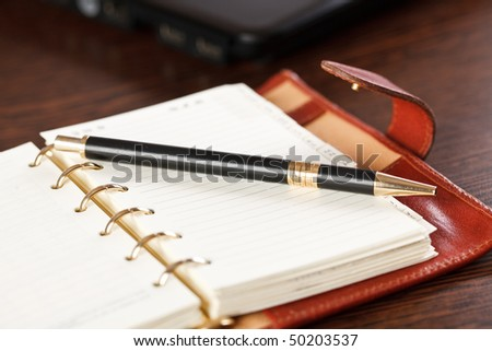 open notebook and pen on table - stock photo