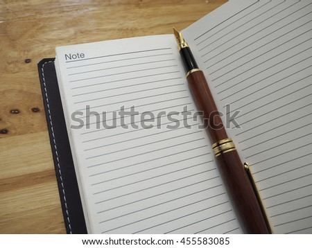 open notebook and pen on wood working desk in office