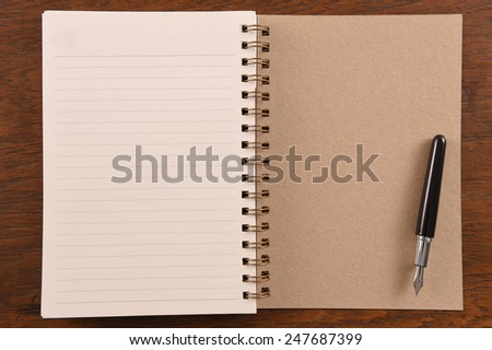 Open notebook and pen on wooden background.