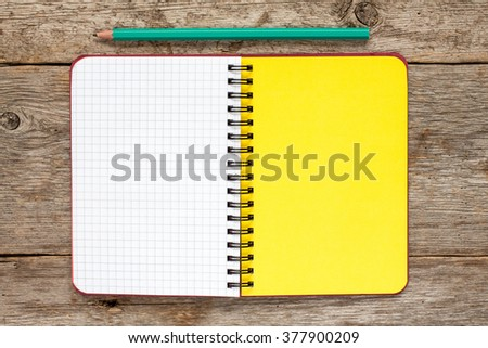 Open notebook and pencil on the old wood background.Top view.