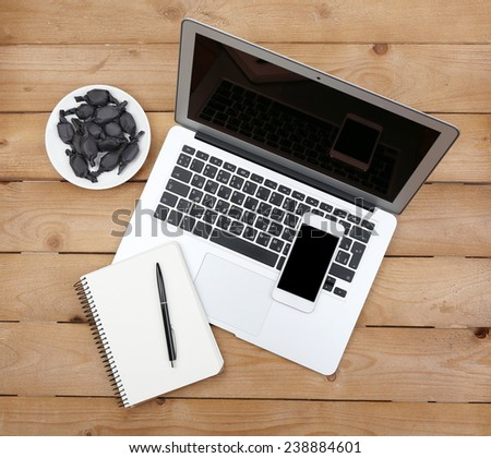 Open notebook, diary and smart phone with saucer of candies on wooden background, top view - stock photo