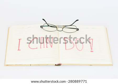 """Open notebook (diary) with text """"I can do!"""", and glasses on the top - stock photo"""