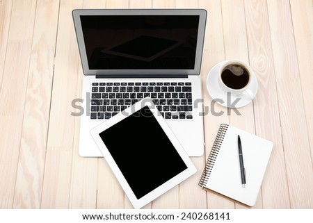Open notebook, digital tablet, diary and a cup of coffee on wooden background, top view - stock photo