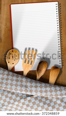Open notebook for recipes or menu on an wooden table with checkered tablecloth and kitchen utensils, fork, spoons and ladles - stock photo