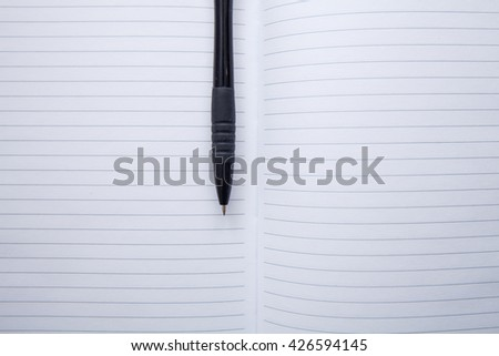 Open notebook in the line and a black pen - stock photo