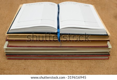 Open notebook on a stack of books, burlap background