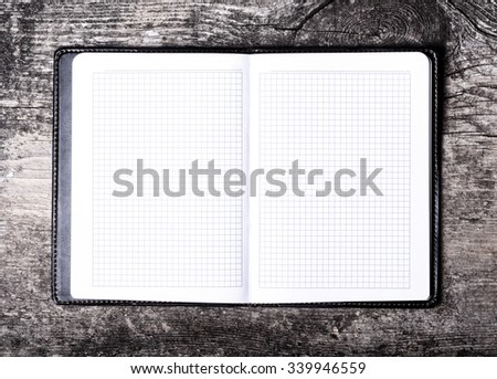 Open notebook on old wooden table - stock photo
