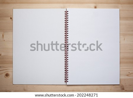 Open notebook on wooden table. - stock photo