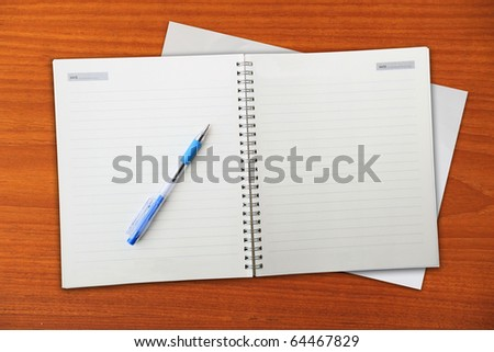 Open notebook on wooden table background. - stock photo