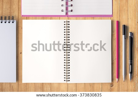Open notebook pencil  and pen on wood table for background and text - stock photo
