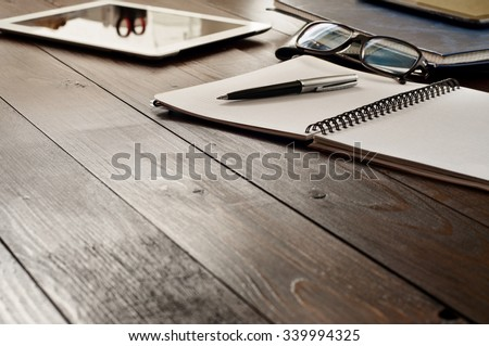 Open notebook, tablet computer, glasses and folders on the office table. Top view with copy space. Free space for text. Office workplace - stock photo