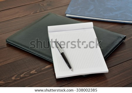 Open notebook with blank page with a pen on the leather business folder on the office table close up. Top view. Free space for text. Copy space - stock photo