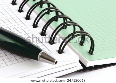 Open notebook with blank pages and with green pen, isolated on white background - stock photo
