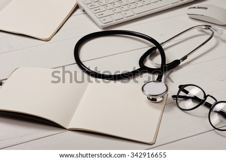 Open notebook with blank pages with stethoscope and glasses on a white doctor's desk close up. Free space for text. Copy space. Top view