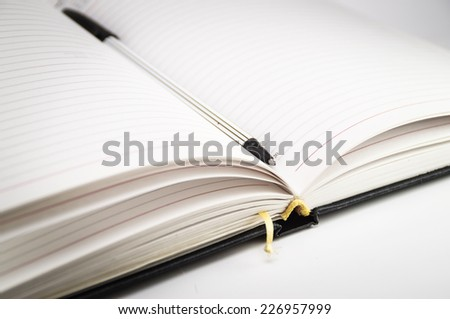 Open notebook with bookmark and pen closeup on a white background. Photo. - stock photo