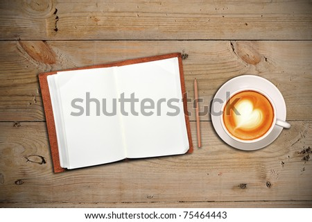 Open notebook with cup of coffee on a wooden floor - stock photo