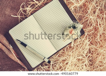 Open notebook with cup with pen