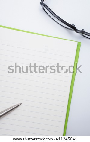 Open notebook with metallic ball pen and glasses, Copy space in center - stock photo