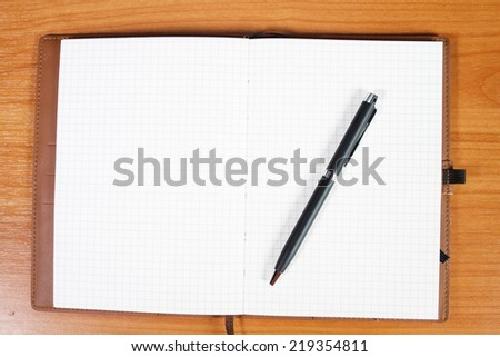 open notebook with passport and pen over wooden background - stock photo
