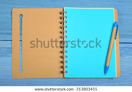 Open notebook with pen on blue wooden table - stock photo