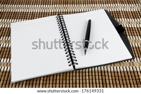Open notebook with pen over textured bamboo mat - stock photo