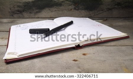 open notebook with pen, shallow depth of field, focus on pen tip
