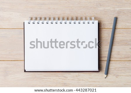 Open notebook with pencil on wooden table