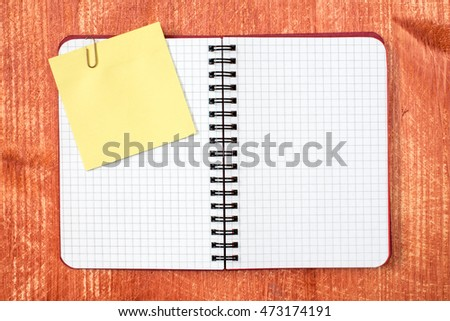 Open notebook with sticky note on red wooden background