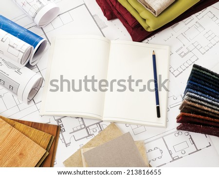 Open notepad, blueprints, wood, material and stone samples - stock photo