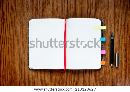 Open notepad on wooden table with copy space - stock photo
