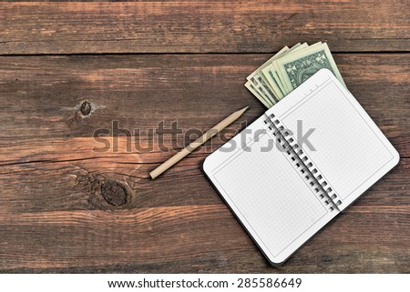Open Notepad, Pencil And Dollars Cash On Rough Wood Background With Copy Space Top View - stock photo