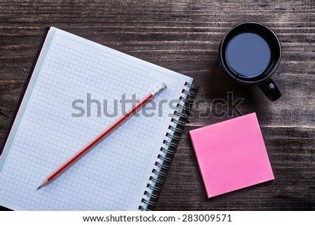 Open notepad pencil reminder note and cup of coffee on wooden board office concept  - stock photo