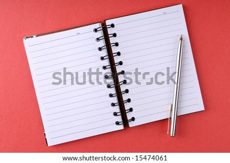 Open notepad with a pen. Isolated on red background. - stock photo