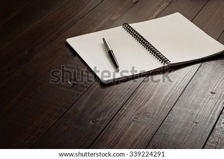 Open notepad with a pen on a brown wooden office desk. Copy space. Free space for text - stock photo