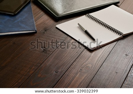 Open notepad with blank pages with a pen on the office wooden desk close up. Top view - stock photo